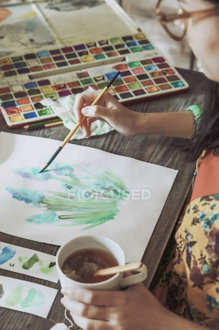 Woman drinking tea and painting — Stock Photo