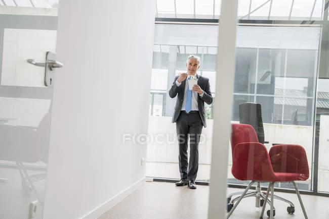 Homme d'affaires debout et manger de la nourriture à emporter — Photo de stock