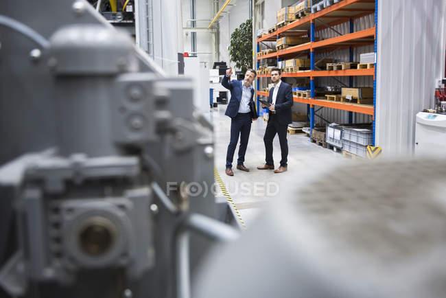 Бизнесмены обсуждают на заводе — стоковое фото