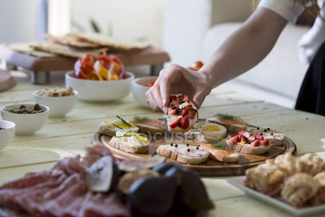 Hand reaching for appetizers — Stock Photo