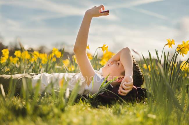 Boy lying in daffodil field — Stock Photo