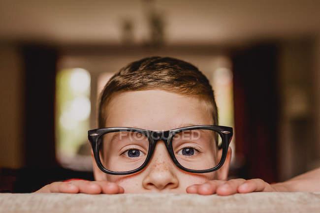 Подглядывающий мальчик в огромных очках — стоковое фото