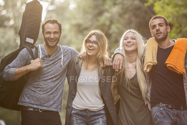Four happy friends walking on path — Stock Photo