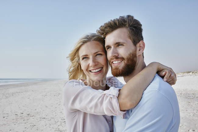 Coppia abbracci sulla spiaggia — Foto stock