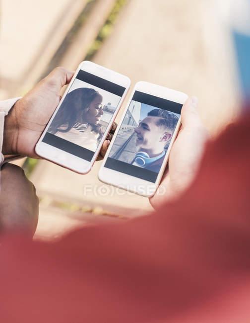 Mãos segurando smartphones com fotos do casal — Fotografia de Stock