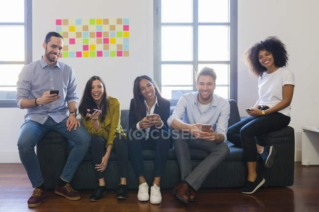 Colleagues sitting with cell phones — Stock Photo