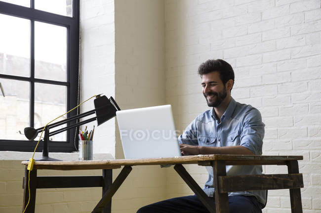 Man sitting at desk working with laptop — Stock Photo