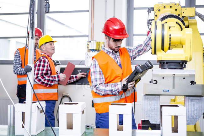 Three men in factory with industrial robot — Stock Photo