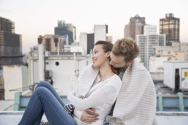 Couple embracing in front of cityscape — Stock Photo