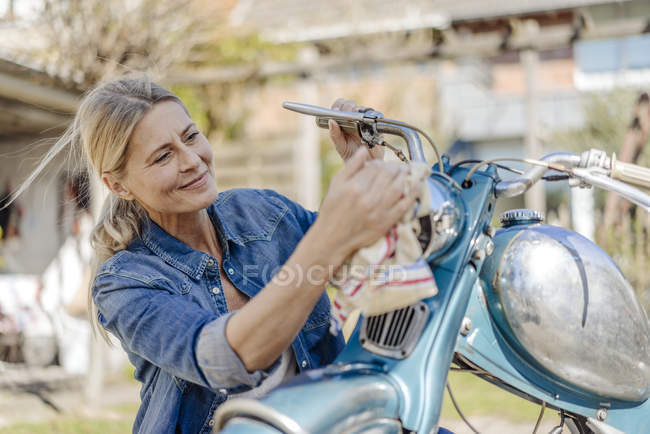 Woman cleaning vintage motorcycle — Stock Photo