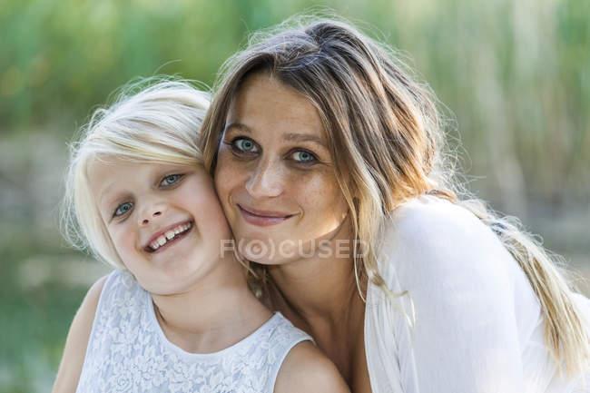 Портрет посміхаючись, мати і дочка на відкритому повітрі — стокове фото