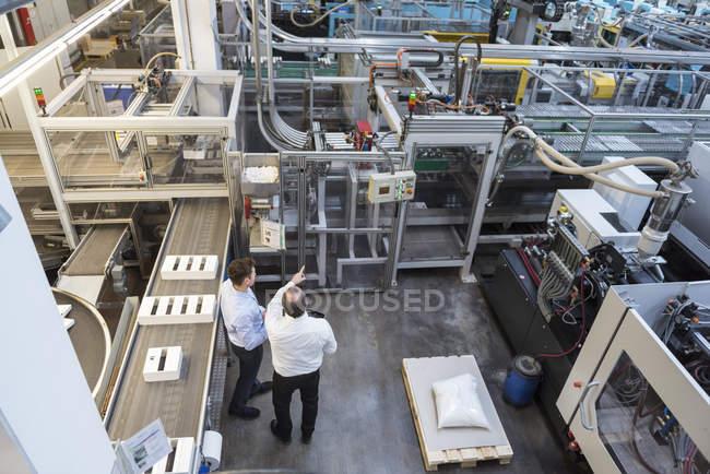 Мужчины обсуждают производство на заводе — стоковое фото