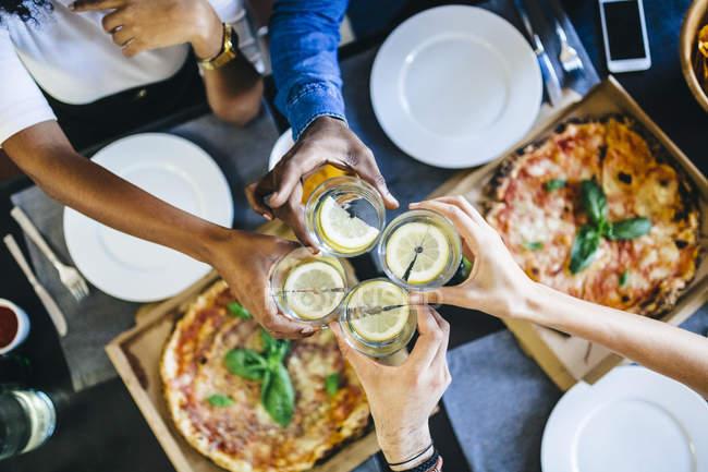 Amigos, comer pizza e tilintar de copos — Fotografia de Stock