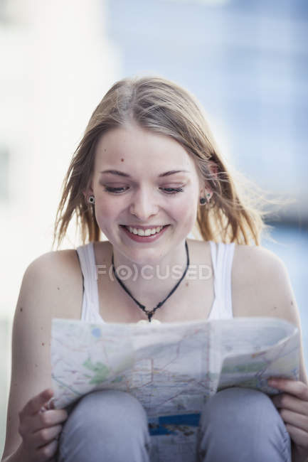 Young girl traveling alone, looking at map — Stock Photo