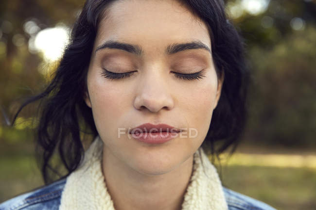 Woman sanding with eyes closed — Stock Photo