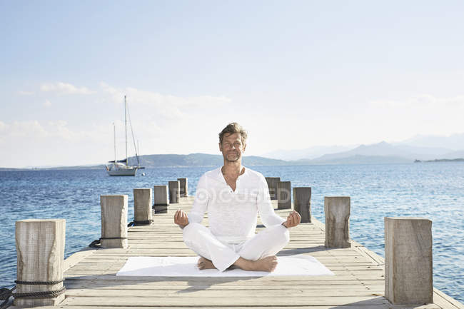 Man doing yoga exercise on jetty — Stock Photo