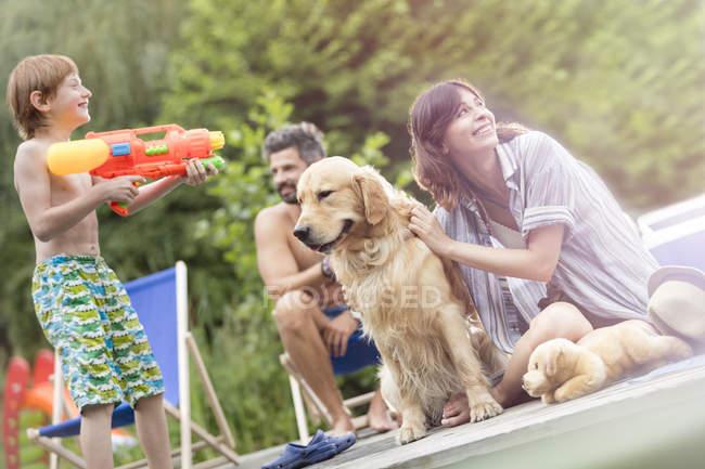 Famiglia felice con il cane si diverte con una pistola ad acqua — Foto stock