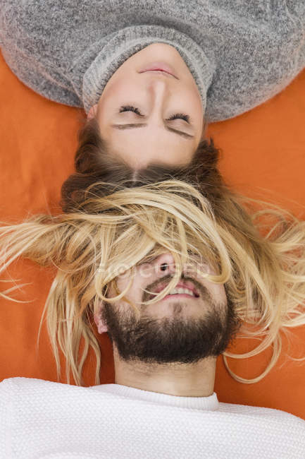 Casal deitado no cobertor laranja — Fotografia de Stock