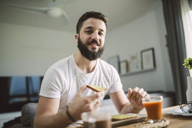 Young man having breakfast at home — Stock Photo