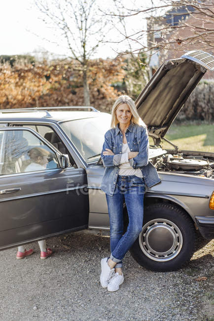 Woman with girl standing near vintage car — Stock Photo