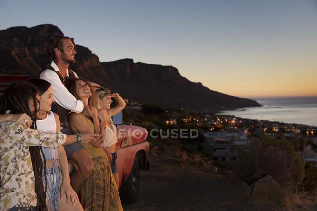 Les jeunes gens debout sur la côte près de van et de coucher du soleil — Photo de stock