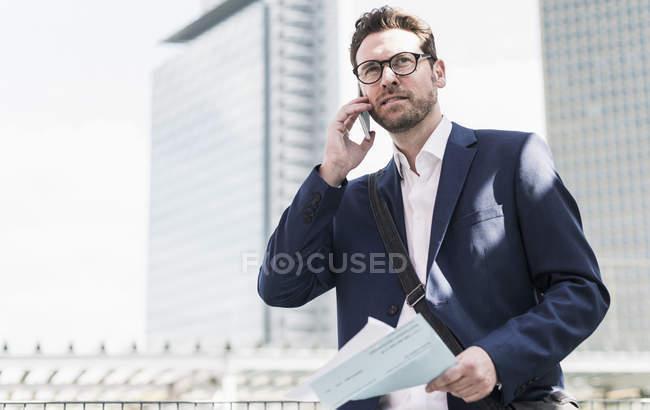 Uomo d'affari che utilizza il telefono al livello del parcheggio — Foto stock