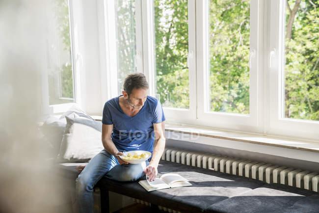 Человек с книгой обедает — стоковое фото