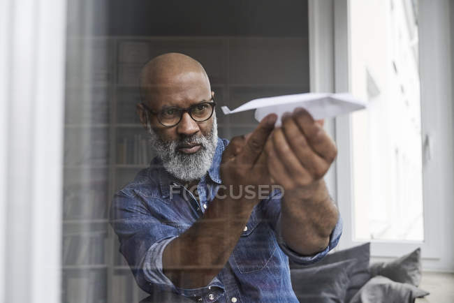 Mature man plying with paper plane — Stock Photo