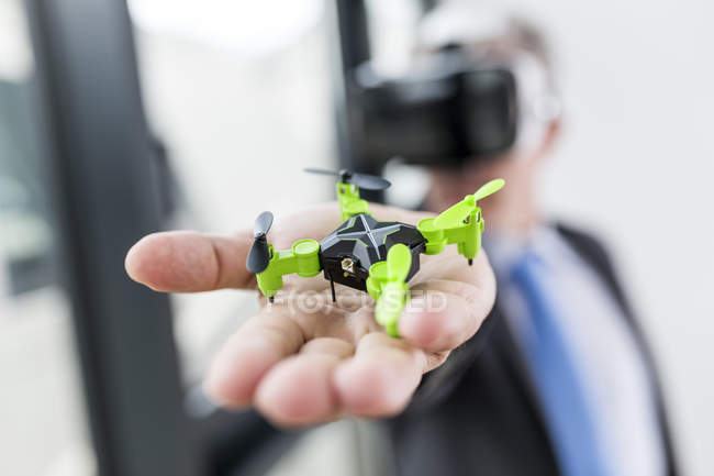 Businessman looking at drone through VR goggles — Stock Photo