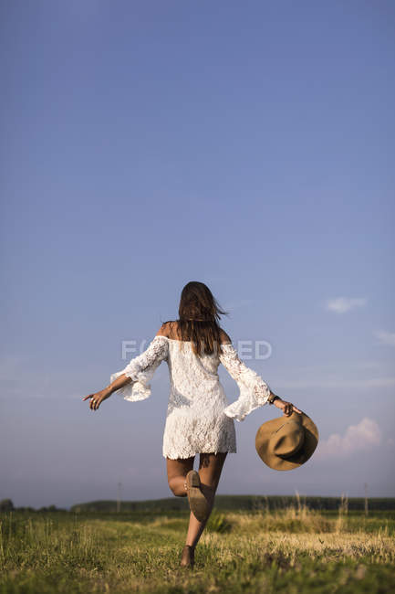 Woman running in summer field — Stock Photo