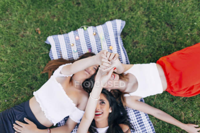 Friends lying on blanket and raising arms — Stock Photo