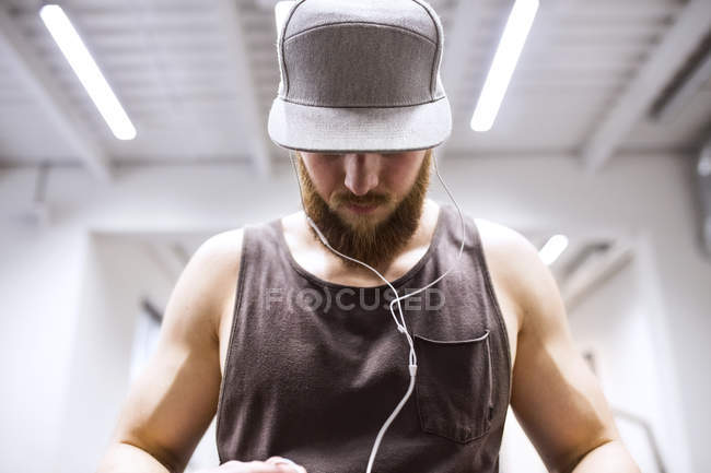 Young athlete using earphones in gym — Stock Photo