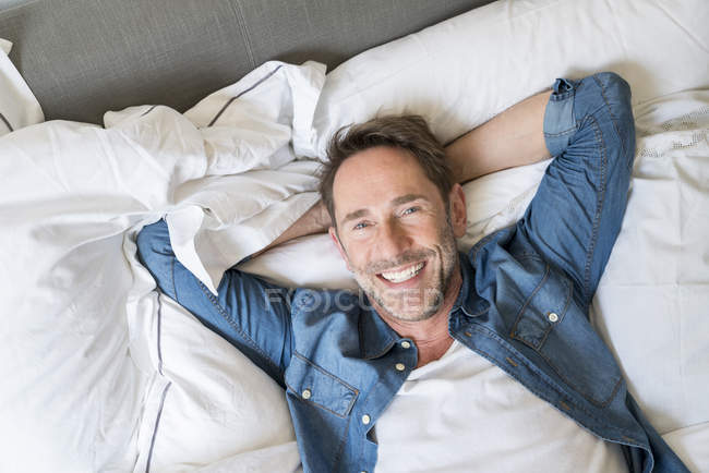 Homme couché sur le lit — Photo de stock