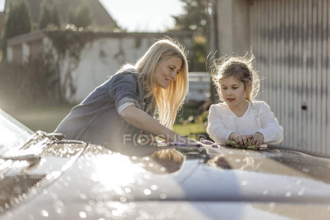 Woman and girl cleaning car — Stock Photo