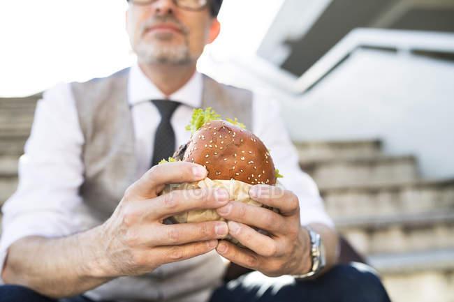 Businessman eating hamburger — Stock Photo