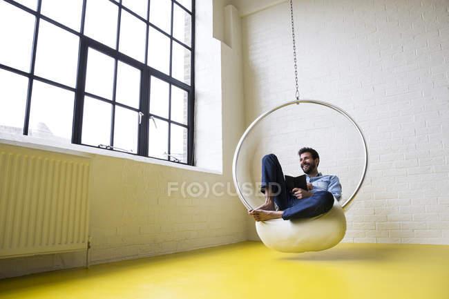 Homme avec livre sur chaise d'oscillation — Photo de stock
