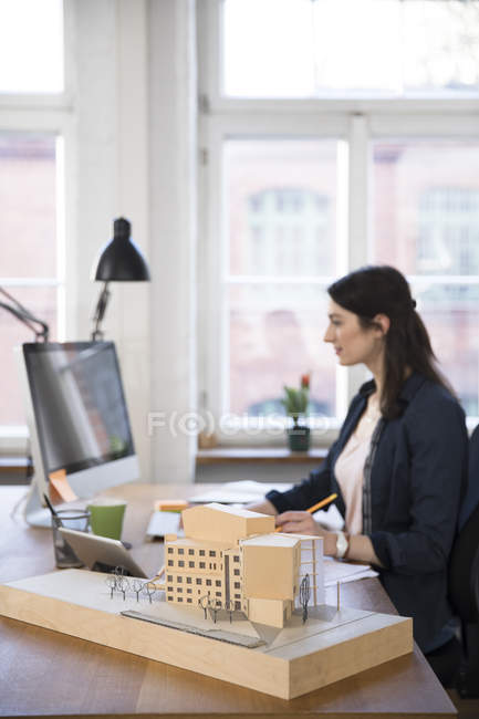 Architectural model and woman working — Stock Photo