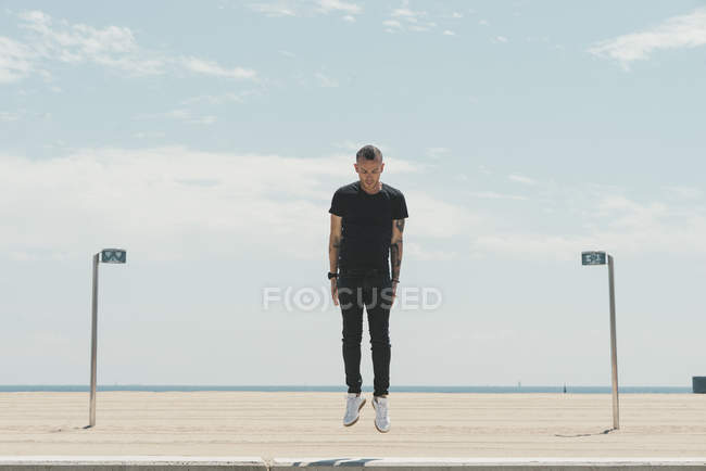Young man with mohawk haircut and tattoos jumping in the air at the coast — Stock Photo