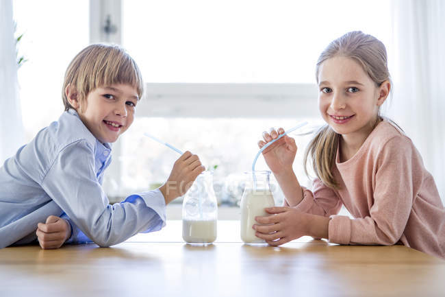 Brother and sister drinking milk — Stock Photo