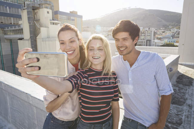 Люди принимают selfie перед городской пейзаж — стоковое фото