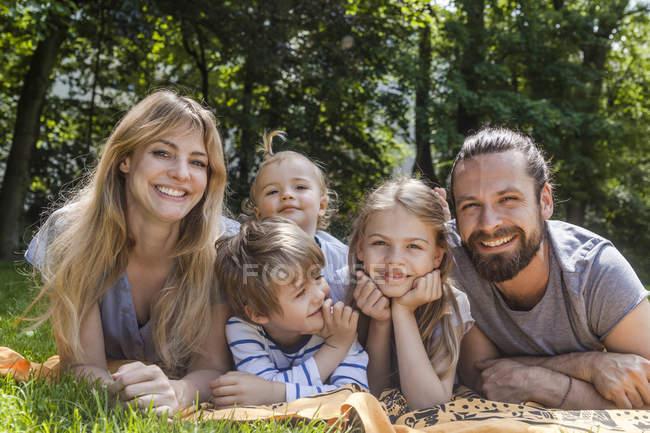 Família feliz deitado no prado — Fotografia de Stock