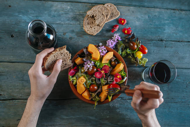 Hands and mixed salad with bread — Stock Photo