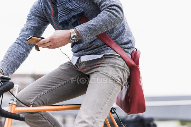 Businessman riding bicycle in city — Stock Photo