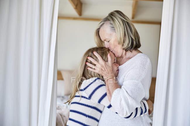 Grandmother kissing granddaughter — Stock Photo