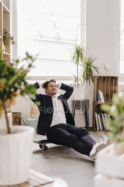 Businessman sitting on skateboard — Stock Photo