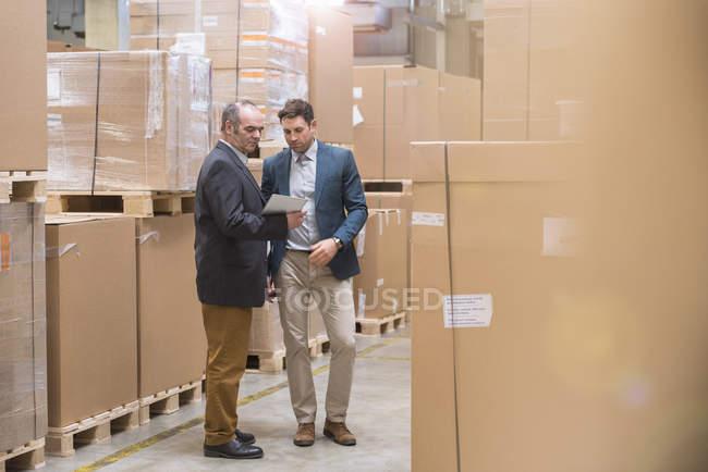 Deux hommes regardant la tablette dans l'entrepôt de l'usine — Photo de stock