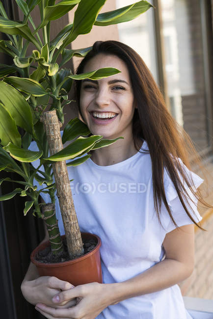 Laughing woman with flowerpot — Stock Photo