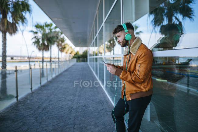 Man using smartphone and wearing headphones — Stock Photo