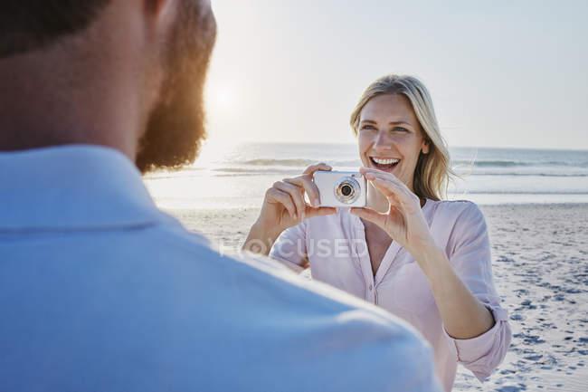 Woman taking photos of man — Stock Photo