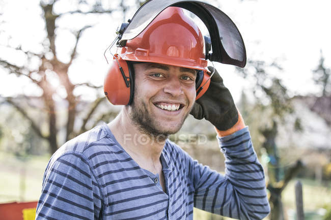 Young man wearing working helmet and ear defenders, portrait — Stock Photo